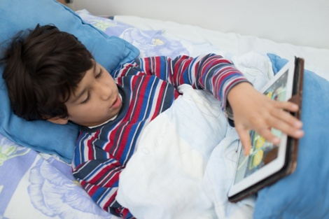 Child patient in hospital bed using tablet-1