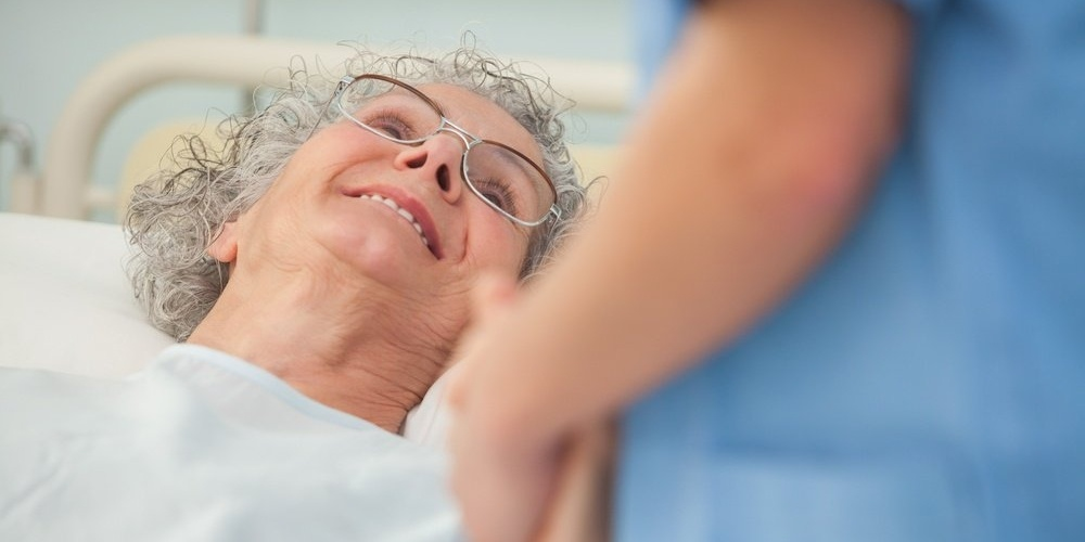 Elderly female patient looking up at nurse from hospital bed-367477-edited