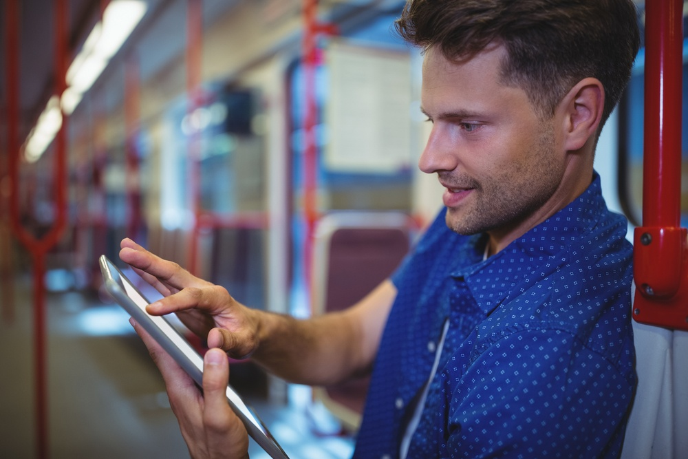 Handsome man using digital tablet while travelling in train