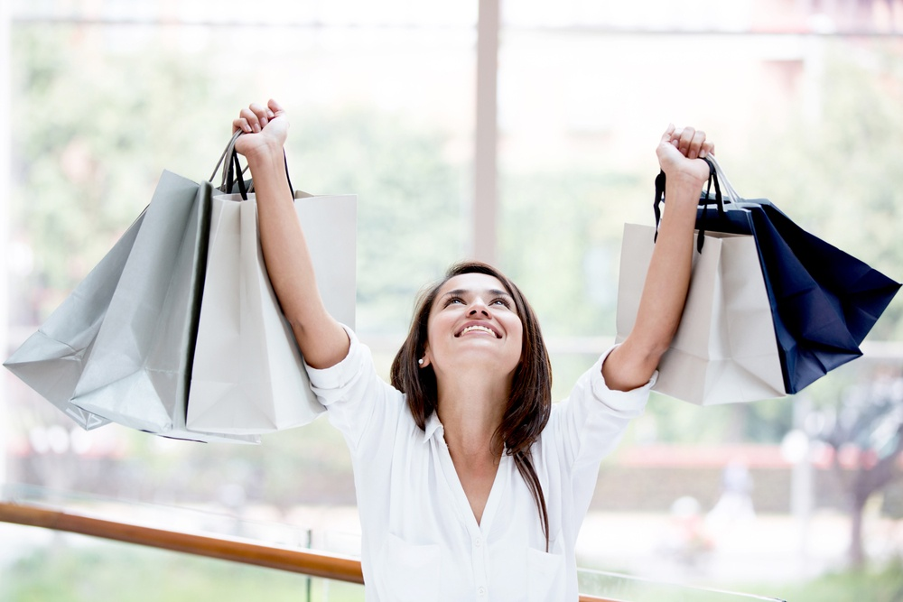 Happy shopping woman with arms up holding bags