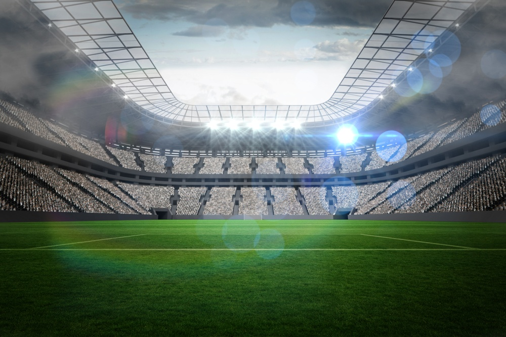 Large football stadium with lights under cloudy sky
